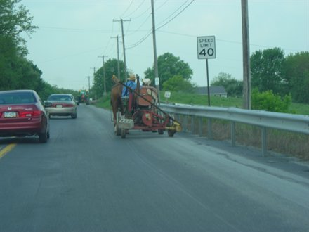amish man driving farm equipment on the side of a road in lancaster