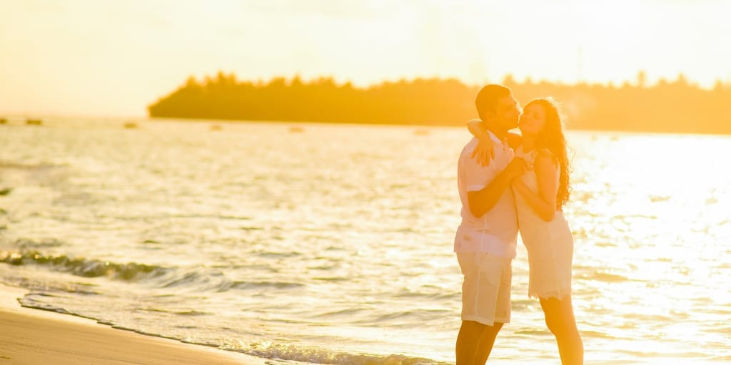 couple kissing, with sunset and beach in background