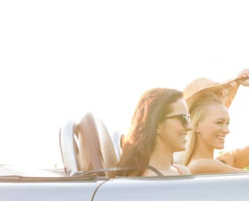 two girls in convertible driving away with lots of sunshine in sky