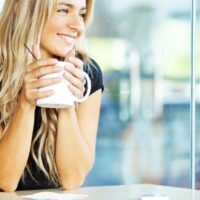 young woman with coffee, smiling, looking out of window at desk thinking about why do people want to be rich