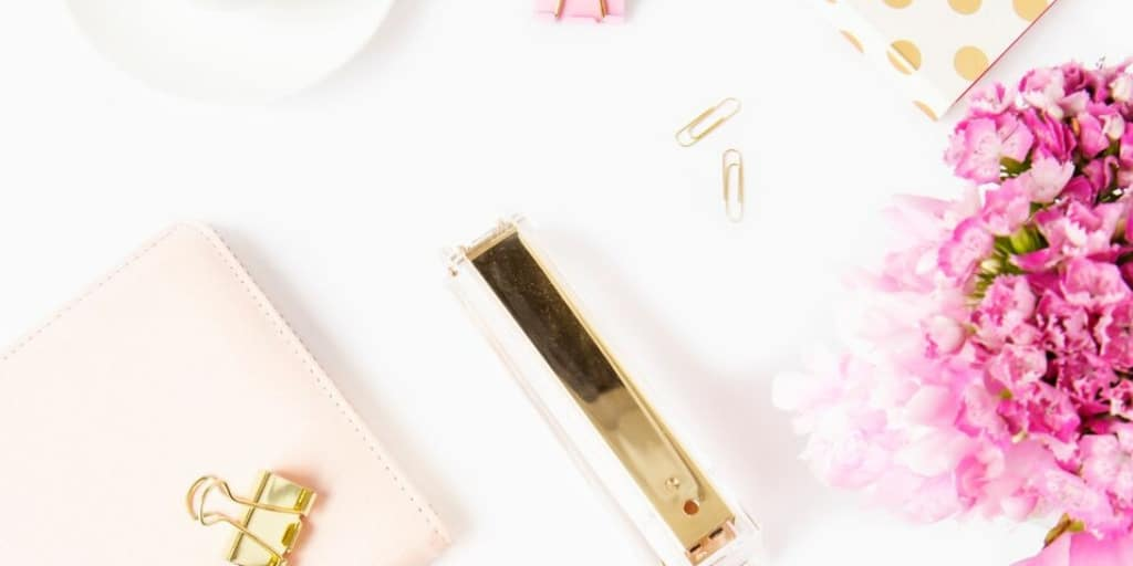 white desktop with pink flowers, gold stapler, and gold binder clips