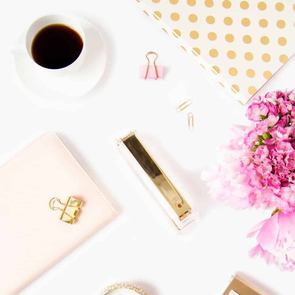 white desktop with coffee, gold stapler and pink notebook