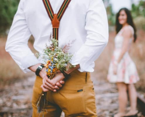 man holding floral bouquet behind back as surprise