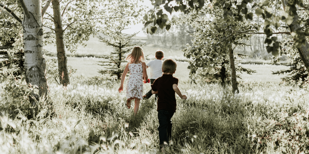 group of three kids running through a meadow for cheap family activities