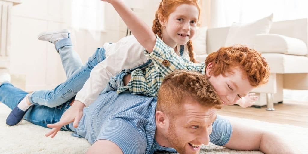 family of father and two kids playing airplanes on the floor, things families do together at home