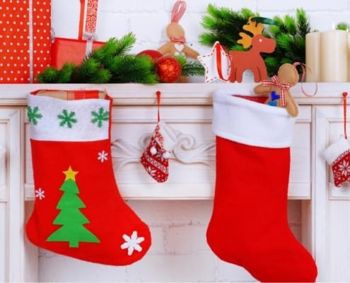white fireplace with mantel, and two Christmas stockings for men hanging