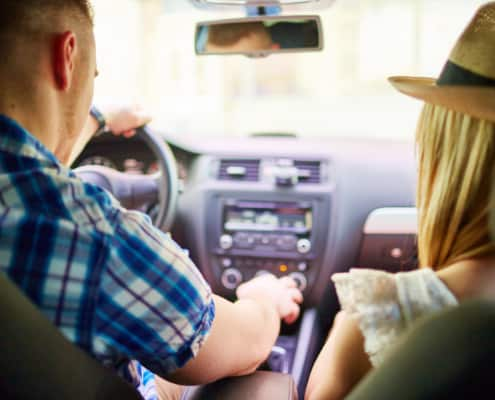 Young couple doing a car trip, view from rear seat