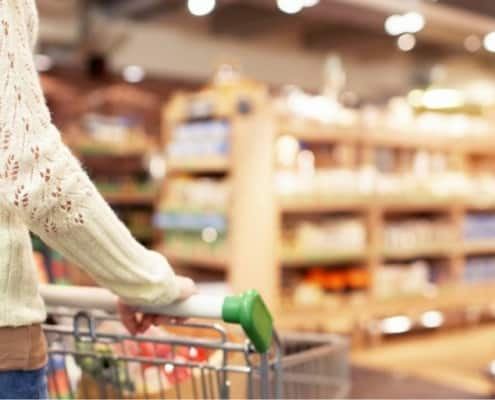 image of woman pushing shopping cart through grocery store