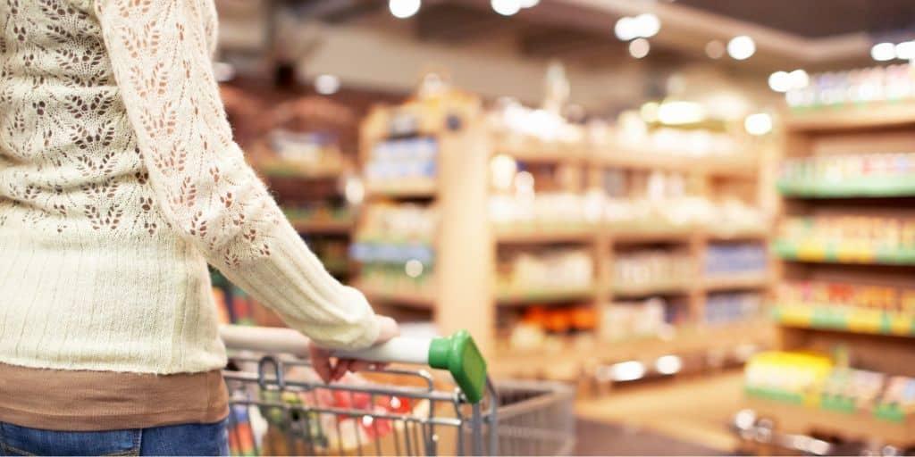 image of woman pushing shopping cart through grocery store