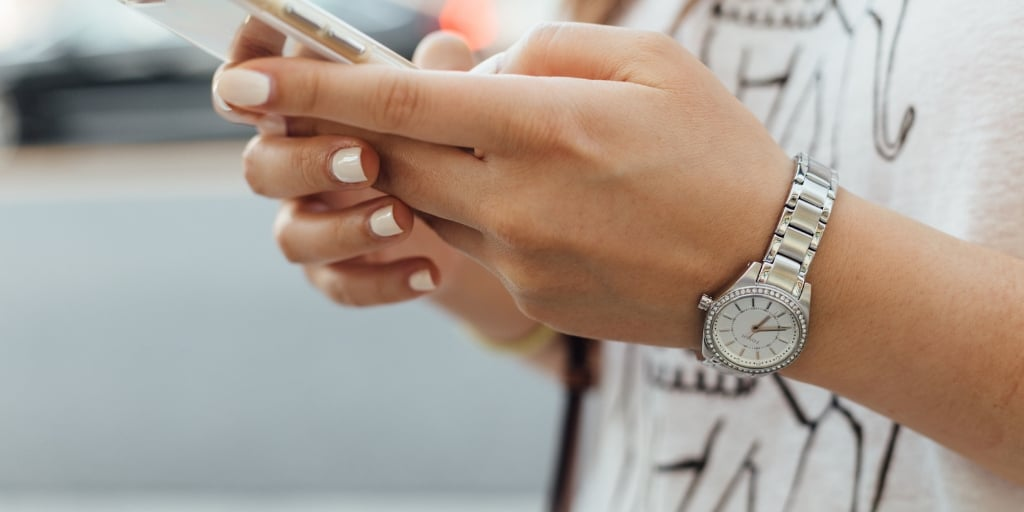 woman with manicured nails holding an iphone, texting