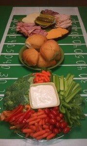 three DIY Superbowl Party trays with veggies, dips, sandwich fixings, on top of a homemade football field cloth