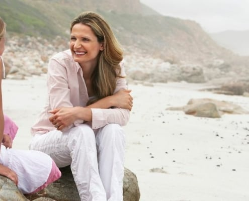 image of mother and daughter on a beach rock, smiling and talking on Mother's Day