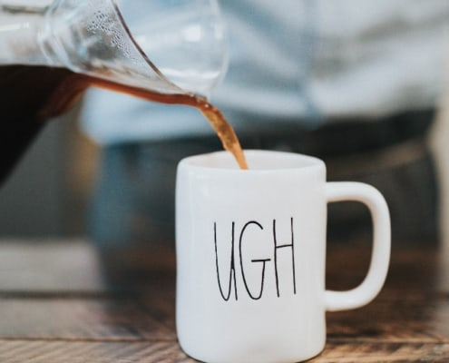 "coffee mug on wooden table with ""ugh"" on it, and someone pouring coffee in"