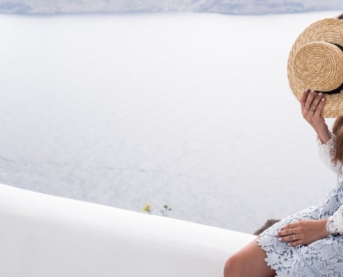 woman sitting on white ledge with hat on her face to cover shame, ocean background