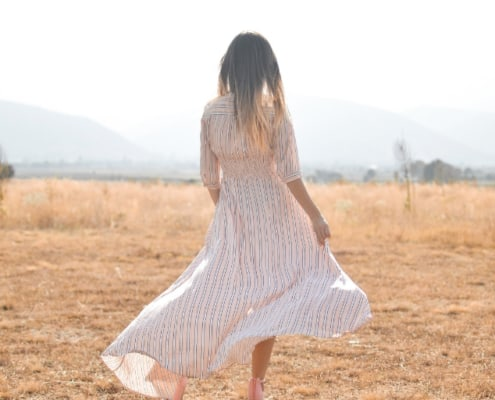 a woman in a white summer dress out in a meadow thinking about money goals