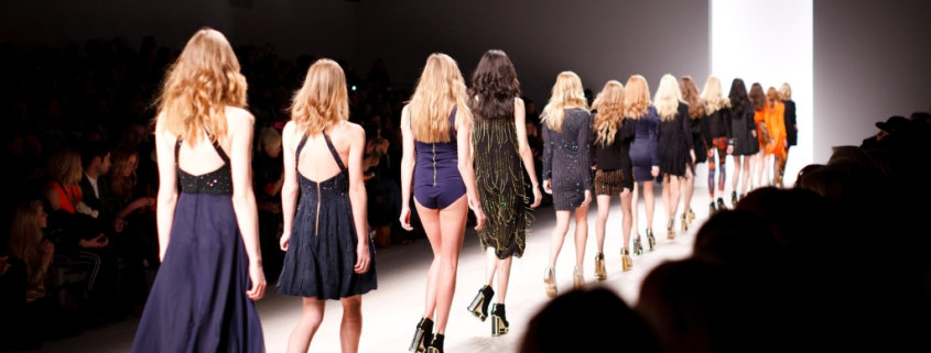 line of runway models, all in navy blue clothing