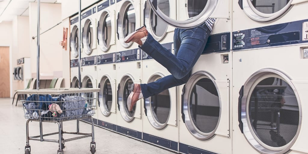 woman at laundromat, reaching whole body into washer