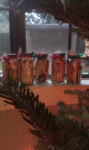 5 spaghetti jars of kindness wrapped with a red ribbon and a candy cane