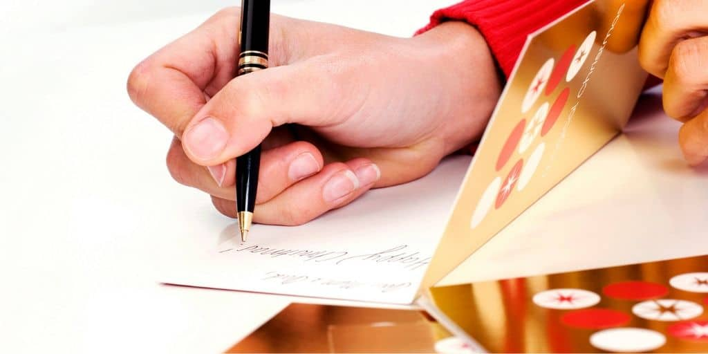 woman's hand writing holiday card messages