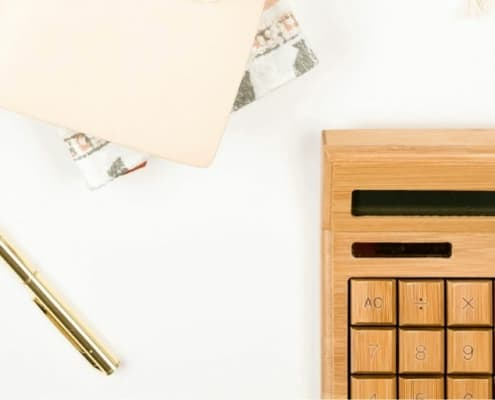 white desktop with wooden calculator and pen/notepad