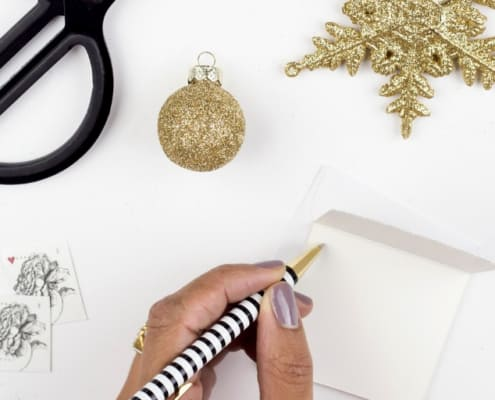 woman's hand writing financial new years resolution at desk with star and scissors