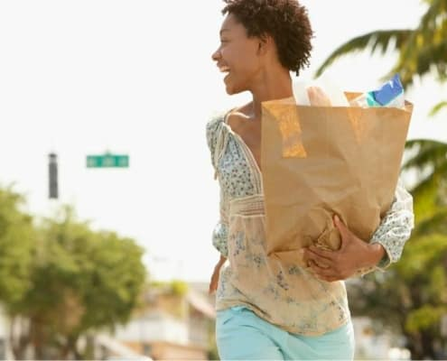 young woman with grocery bags from extreme couponing trip