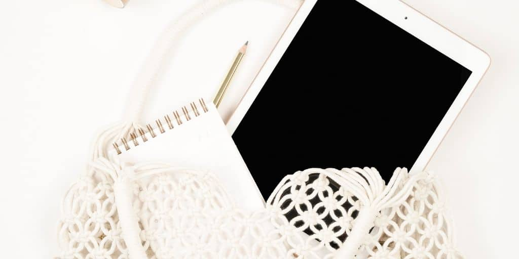 iPad with notepad, on white desk, in white crochet bag