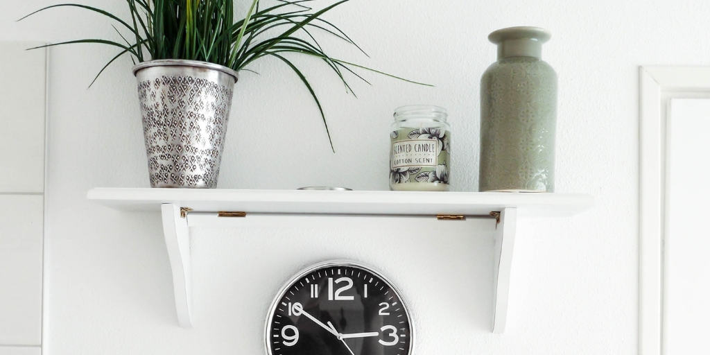 white mantel with plant, clock, and two vases