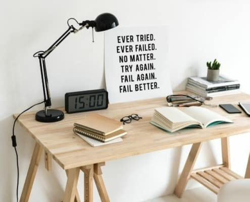 wooden desk with reading lamp and inspirational poster