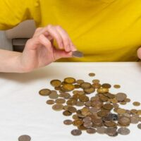 woman in yellow shirt counting pennies from red piggy bank saved from extreme frugal living