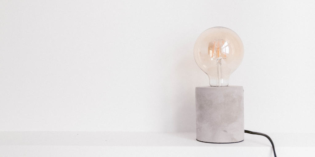 image of a light bulb on extremely frugal desktop, minimalist