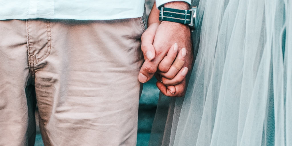 a couple holding hands, she wearing a blue ballet skirt
