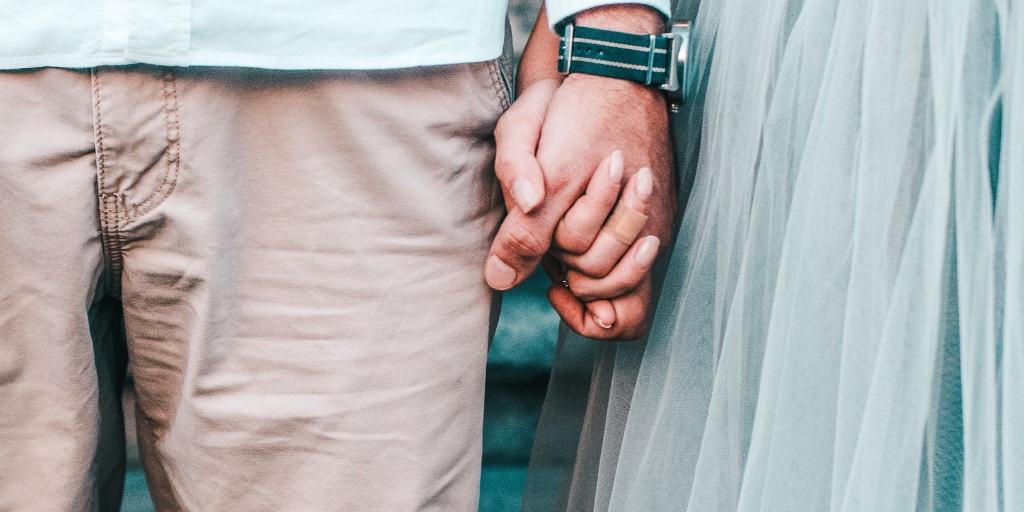 a couple holding hands, she wearing a blue ballet skirt