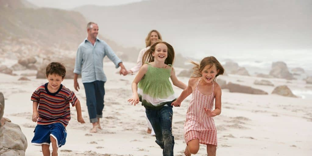 young family running on beach during early retirement