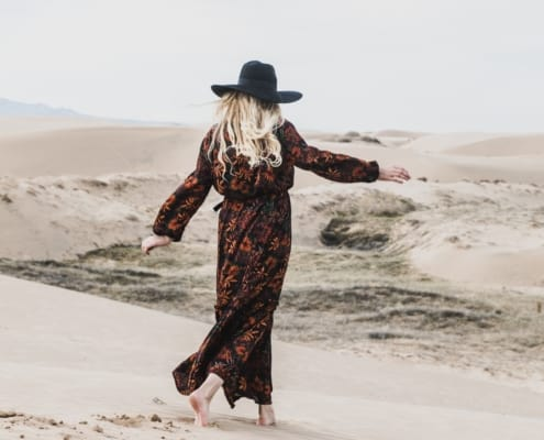 woman in large hat walking leisurely on beach with arms out