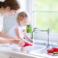 woman with toddler, using water at kitchen sink, looking for ways to save money on water bill