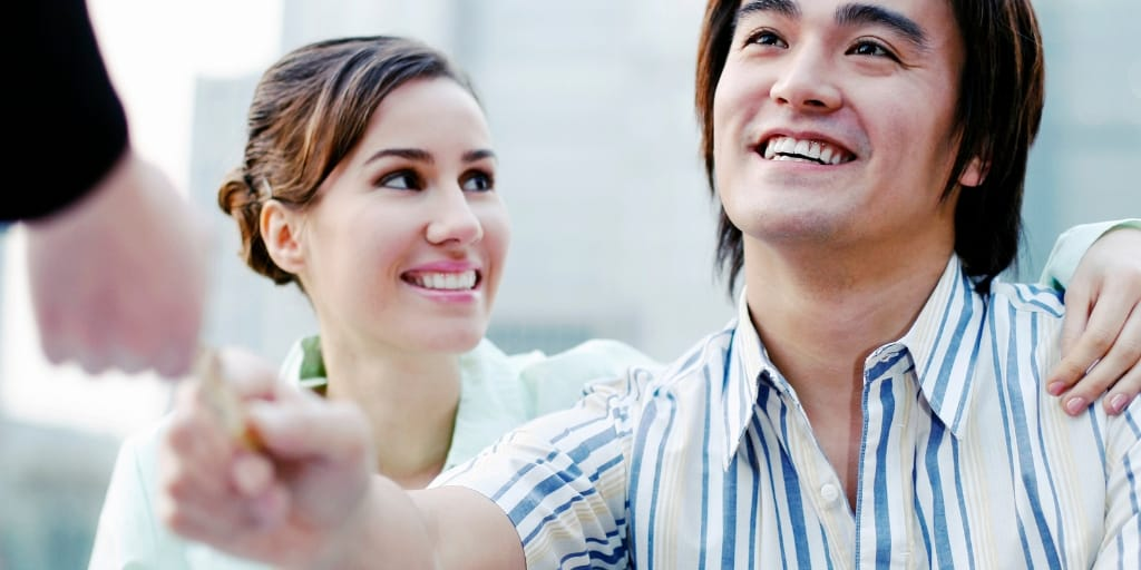 young couple, asian male handing over credit card to banker