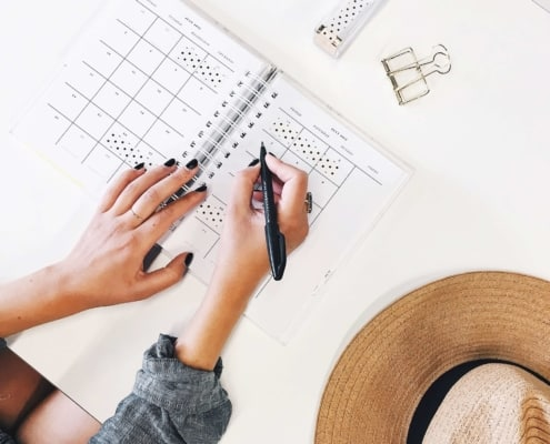 white desktop with woman writing in her planner, hat on desk