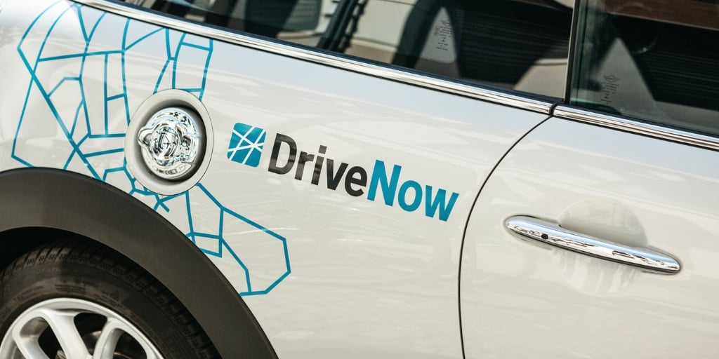 "white car with car advertisement wrapping ""Drive Now"""