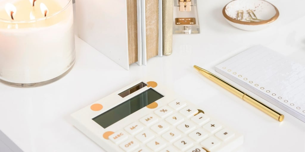 white desk with white and gold calculator, gold pen, binders, and a candle