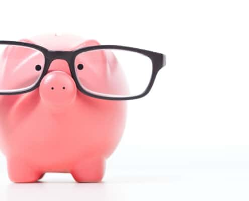 pink piggy bank with black glasses, on white background