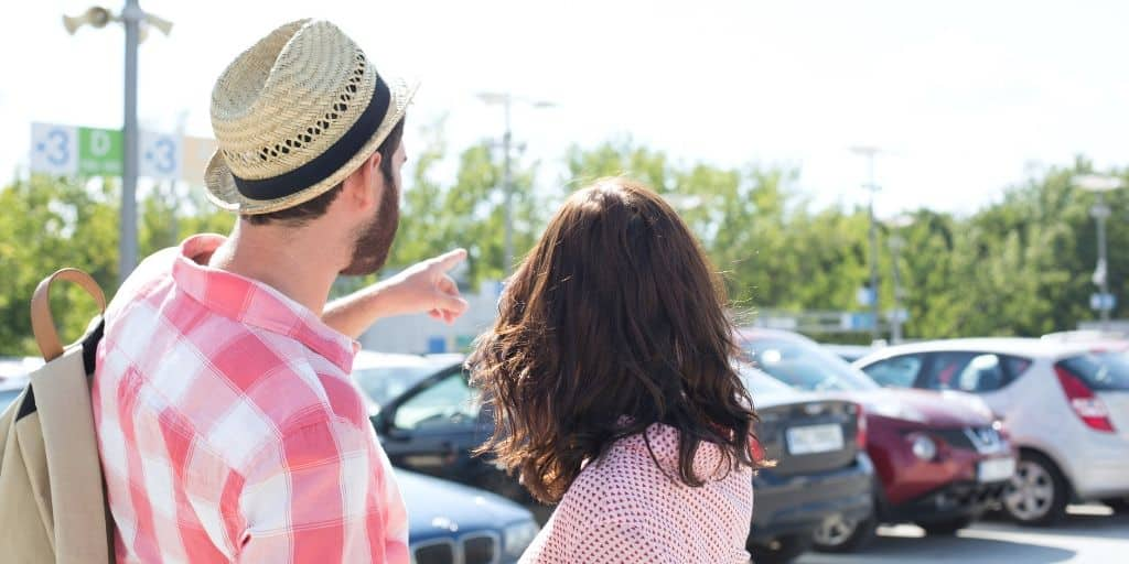 young couple in rental car parking lot, pointing to a car