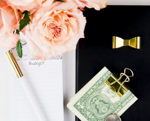 desk with peach roses, money clip, money, notepad and pen