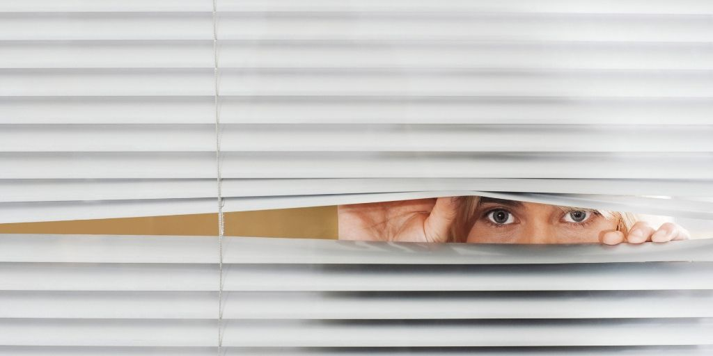 woman peering through a blind on the window