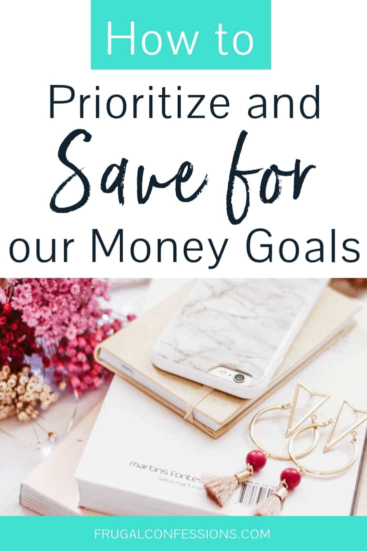 """desk with books, dark pink flowers, and earbuds with text overlay """"how to prioritize and save for money goals"""""""