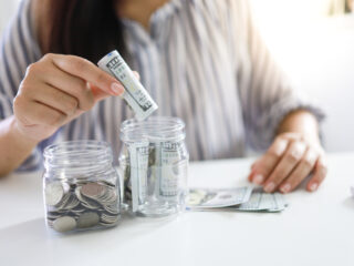 woman's hands putting money into two savings jars for multiple savings goals