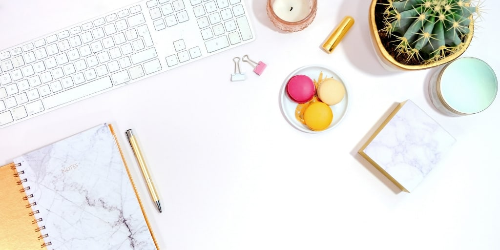 white desk, white keyboard, colorful macaroons, plant, notepad