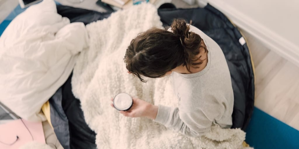 woman sitting on comfy bed under blanket with coffee