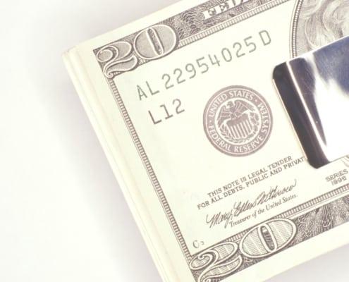 money clip with $20 bills on white background