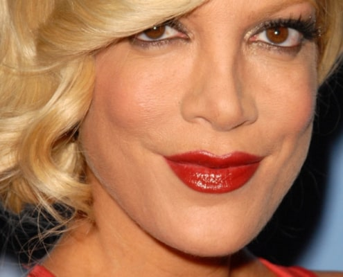 tori spelling with bun on side, red lipstick, blue background